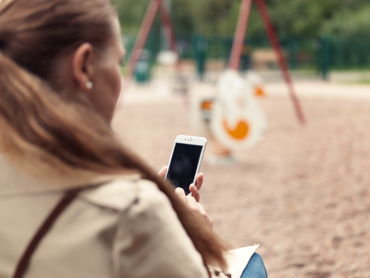Woman in kindergarden browsing mobile phone